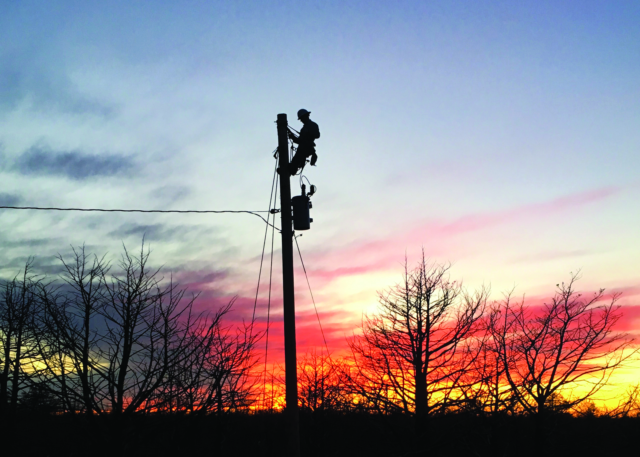 Linemen climbing a pole at sunrise