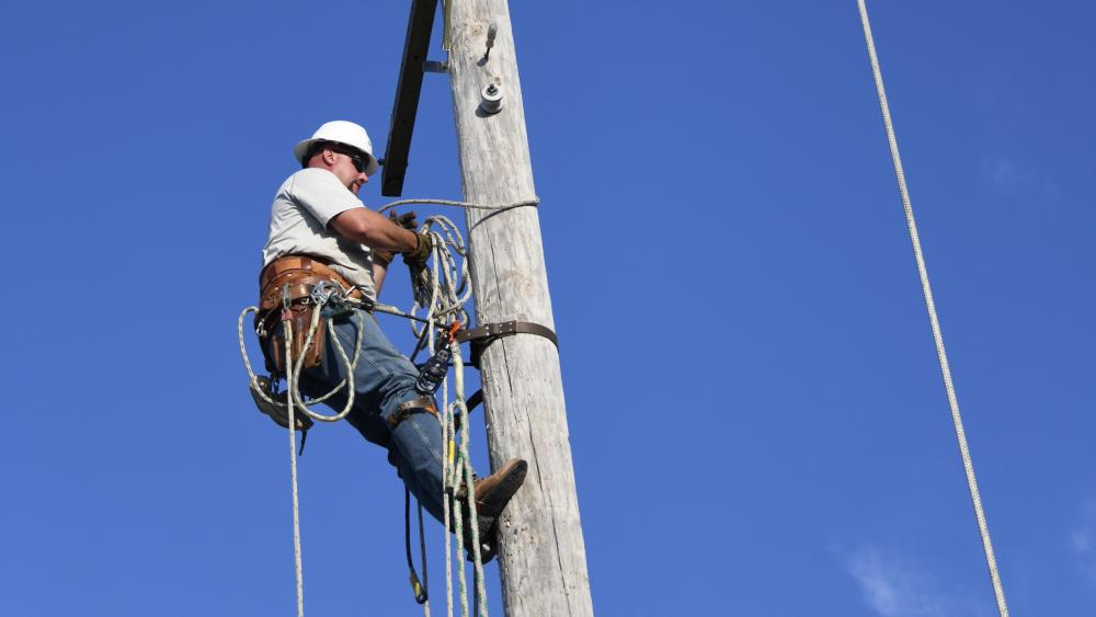 Lineman climbs and electric power pole